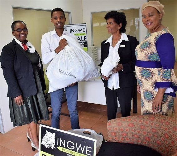 Zama, left, and Mbali Mkhize, Senior Director: Department of Marketing and Communications, right, receiving donations from Ingwe Property staff